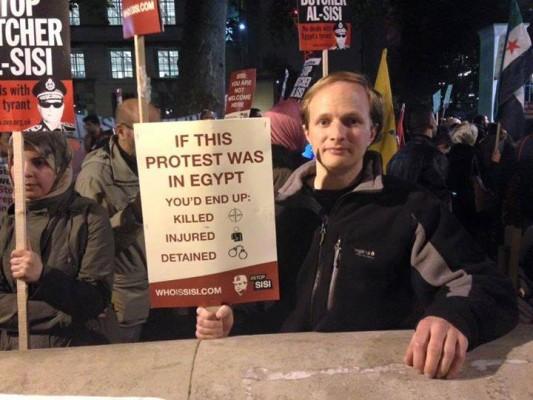 """أحد المتظاهرين في لندن ضد قائد الانقلاب  يرفع لافتة كتب عليها : """"لو كانت هذه التظاهرة في مصر لكنت مقتولًا أومصابًا أو معتقلًا"""""""